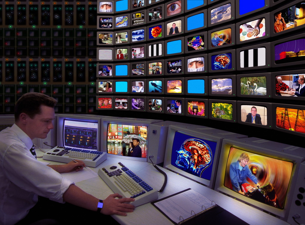 MODEL RELEASED. Television control room. Conceptual composite image of a technician monitoring the output from a television station.