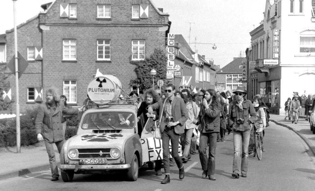 """Der Protest nimmt Fahrt auf: Hinterm R 4 ziehen 1977 zum ersten Osterspaziergang knapp 1000 Kernkraftgegner durch die Kalkarer Straßen. Auf dem Dach des kleinen Kultautos lag ein Fass mit der Aufschrift """"Plutonium"""". Bis zum Schnellen Brüter kam der Zug nicht, dafür hatte ein Polizeiaufgebot von 2000 Beamten gesorgt. FOTO: Evers, Gottfried Brüterdemo"""